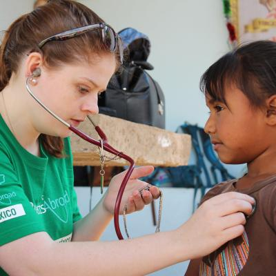 A volunteer measures the heartbeat of a young girl during her medical internship abroad for high school students.